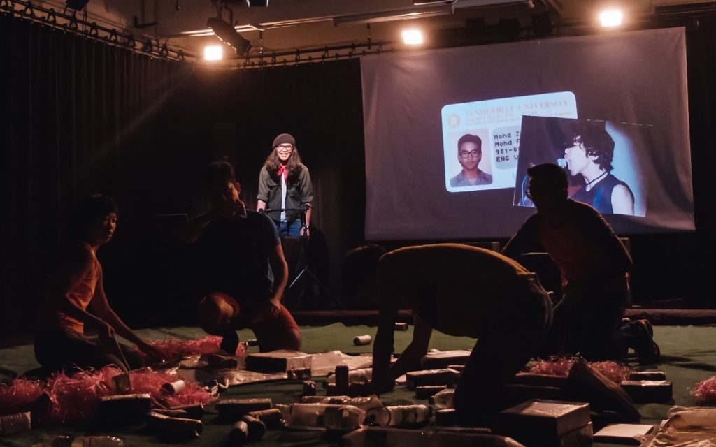 Fahmi Reza projecting images from his past, juxtaposing his nerdy university student and punk rocker selves, Version 2020 (KL). Photo credit: Bryan Chang, courtesy of Five Arts Centre.