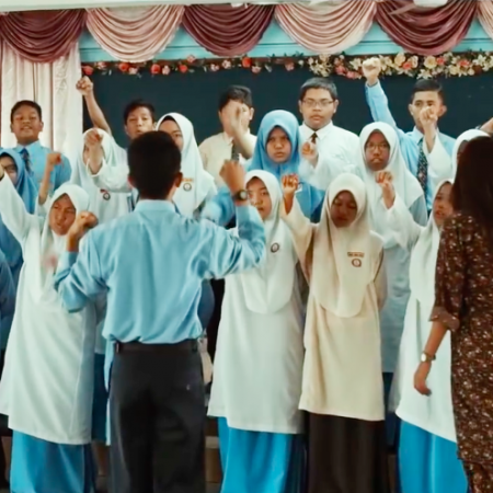The choral speaking students with their arms raised, Zidane and Cikgu Cheryl in front of them - Adiwiraku